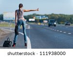 Photo slender young girl trying to stop the car on the road - stock photo