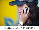 Portrait of pretty girl in profile, wearing a cap talking on a cell phone - stock photo