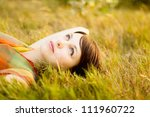 Beautiful girl lying down on grass. Copy space - stock photo