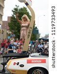 Small photo of Indianapolis, Indiana, USA - May 26, 2018, Linda Vaughn racing beauty queen, on top of a plataform on the back of a classic car, going down the street at the Indy 500 Parade