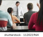 Students studying with professor in classroom - stock photo