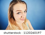 Small photo of A playful young blonde makes a humorous face, expressing disbelief and frustration
