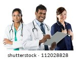 Portrait of happy young Indian doctor holding clip[ board with his team in background. - stock photo