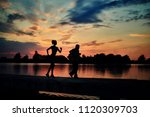 Small photo of Dark silhouettes of scamper runners while sunset near lake. Slim young girl, senior man. Fitness, crossfit exercises. Fit, strong bodies, healthy lifestyle. Outdoors workout on fresh air.