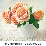 Beautiful fresh roses in a ceramic vase on a table. - stock photo