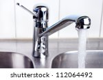 Water flow from chromed steel faucet - stock photo