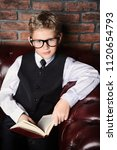 Small photo of Smart boy in elegant suit and glasses sitting on a Chesterfield sofa with a book. Educational concept. Children's fashion. Vintage style.