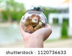 Small photo of Hand hold ball shaped container that contain coins and house model