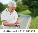 Small photo of Senior sportsman looking on handwatch during morning scamper. Maintaining healthy lifestyle, keeping body sporty, fit, muscular. Wearing sportswear, red headphones, white beard. City park's racetrack.