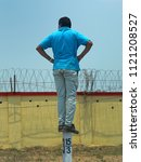 Small photo of CHENNAI, TAMIL NADU, INDIA, MARCH 31, 2018: A man in blue T-shirt balancing on a milestone, arms akimbo and looking at something on the other side of the fenced wall.