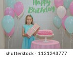 a little girl stands near a... | Shutterstock . vector #1121243777