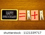 Small photo of Handwriting text Happy Anniversary Motivational Call. Concept meaning Annual Special Milestone Commemoration White paper clip laid woody desk black slate some texts equal and plus mark.