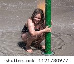 Small photo of Cute smiling eight-year old little girl in swimsuit crouched under water jet holding unto green pole