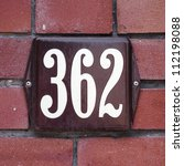 Enameled house number three hundred and sixty-two. White lettering on a brown background. - stock photo