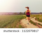 Small photo of Sport teenage girl running outdoor. Young woman running in field at evening. Back view of running lass on meadow at sunset. Sporty girl run away from camera. Fitness training outdoor