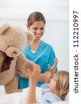 smiling nurse showing a teddy... | Shutterstock . vector #112210997