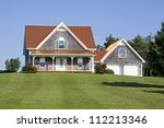 A large country house with a bronze steel roof and an expansive lawn. - stock photo