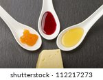 Three different kinds of jam over white spoons and slice of cheese - stock photo