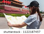 """Small photo of Girl holds a map, on background Tiananmen. Translate chine characters of the left: """"Long Live the People's Republic of China"""" and of the right: """"Long Live the Great Unity of the World's Peoples""""."""