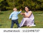 boy giving dandelion to... | Shutterstock . vector #1122498737