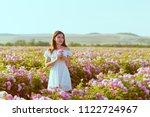 Stock photo beautiful young woman posing near roses in a garden 1122724967