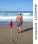 Man on a beach with a red flag - stock photo
