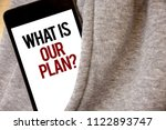 Small photo of Handwriting text writing What Is Our Plan Question. Concept meaning Mission Purpose Agenda Strategize Brainstorming Hoar frost color side pocket cell phone be visible black and red letters.