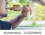 man driving car while eating... | Shutterstock . vector #1123204643