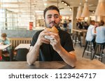 lunch at the cafe. the man eats ... | Shutterstock . vector #1123424717