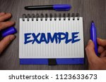 Small photo of Word writing text Example. Business concept for Illustration Sample Model to follow Guide Explanation For instance Man hold holding blue marker notebook page paper ideas wooden background.