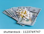 Small photo of dollars pills medicine. Prescription medicine on dollars for pharmaceutical industry concept of high cost for healthcare and medication, top down view. copy space.