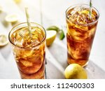 cold iced tea with straws and lemon slices in summer sun. - stock photo