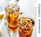 two cold iced tea with straws and lemon slices. - stock photo