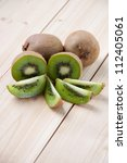 Whole kiwi fruit and his segments on wooden boards, vertical shot - stock photo