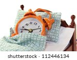 a wooden bed and alarm clock on a white background - stock photo