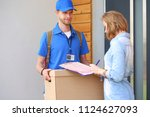 smiling delivery man in blue... | Shutterstock . vector #1124627093