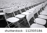 Plastic folding chairs are set up for an outdoor concert - stock photo