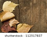 autumn leaves on wooden table - stock photo