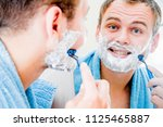 a handsome man shaves his beard ... | Shutterstock . vector #1125465887