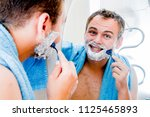 a handsome man shaves his beard ... | Shutterstock . vector #1125465893