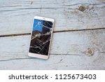 mobile phone with broken screen ... | Shutterstock . vector #1125673403