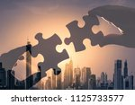 two hands putting puzzle pieces ... | Shutterstock . vector #1125733577