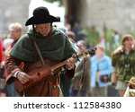 NOGENT LE ROTROU,FRANCE,MAY16:Medieval troubadour tunning his string instrument during a historical reenactment festival near the Saint Jean Castle on May 16,2010 in Nogent le Rotrou,France - stock photo