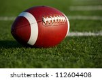American Football on the Field with Yard Lines Beyond - stock photo