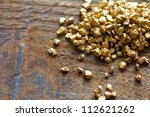 a mound of gold on a old wooden work table - stock photo