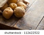Fresh harvested potatoes spilling out of a burlap bag, on a rough wooden palette. - stock photo
