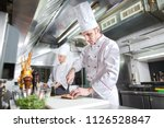 chef cutting meat on chopping... | Shutterstock . vector #1126528847