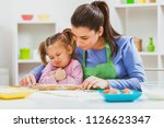 mother and daughter are making... | Shutterstock . vector #1126623347