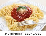 A plate of spaghetti with traditional pomodoro sauce topped with a sprig of basil and parmasan cheese - stock photo