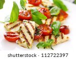 Grilled Halloumi Cheese and roasted tomato salad. - stock photo
